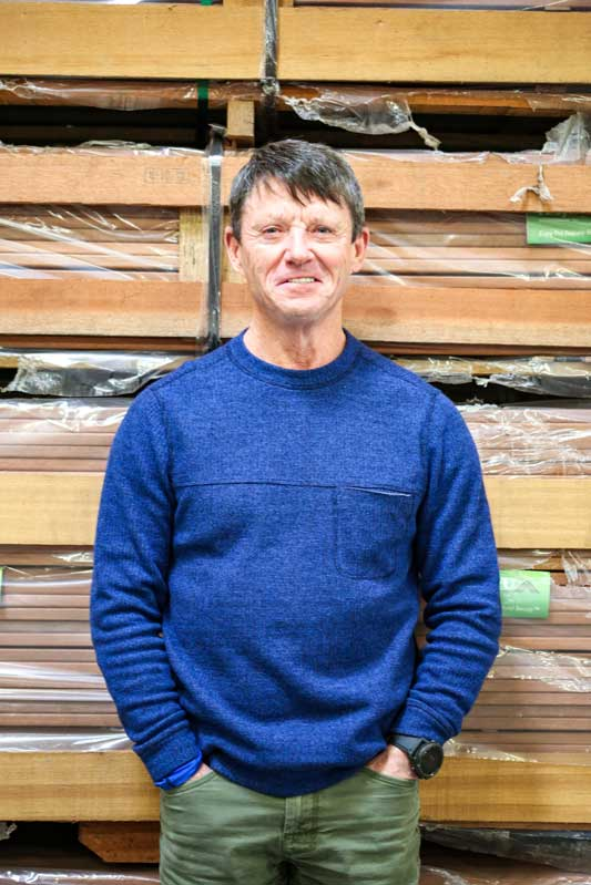 Photo of Steve Wilson, President of Kayu Intl standing in front of keruing apitong hardwood truck and trailer decking in his Oregon Warehouse